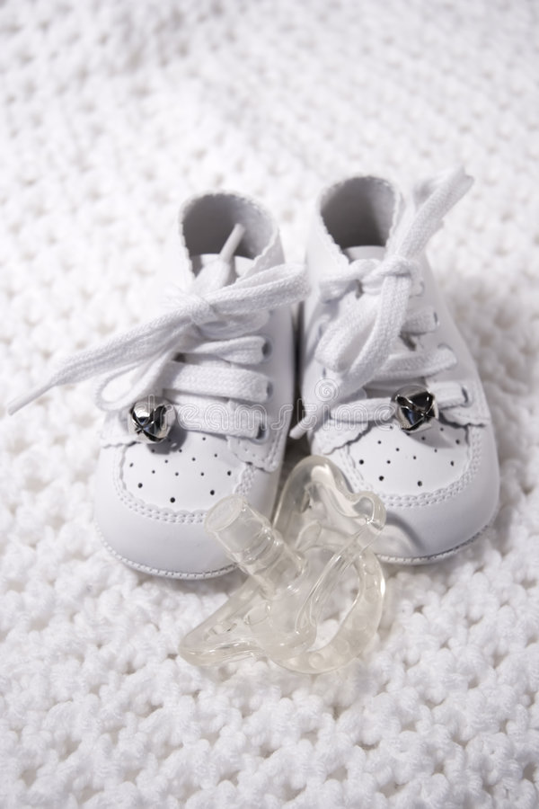 Zapatos de bebé con el pacificador fotografía de archivo libre de regalías