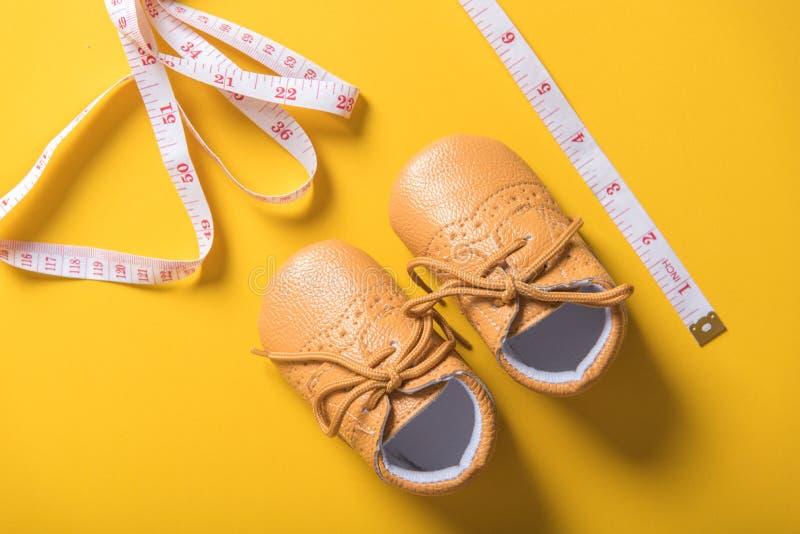 Zapatos de bebé con la cinta métrica en fondo amarillo foto de archivo libre de regalías