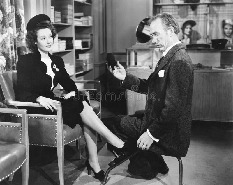 Zapatos de compra de la mujer en una zapatería (todas las personas representadas no son vivas más largo y ningún estado existe Ga imagenes de archivo