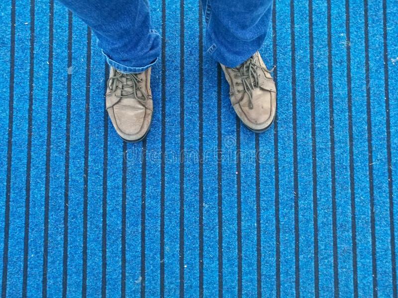 Zapatos de cuero de Brown con los vaqueros que se colocan en la alfombra azul foto de archivo