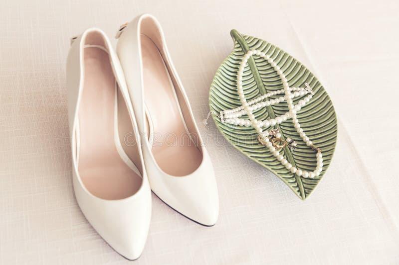 Zapatos de la boda y joyería nupciales de la perla en la tabla imagen de archivo libre de regalías