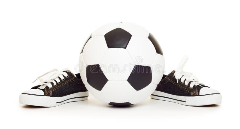 Zapatos de la bola y del deporte de fútbol en blanco imagen de archivo libre de regalías