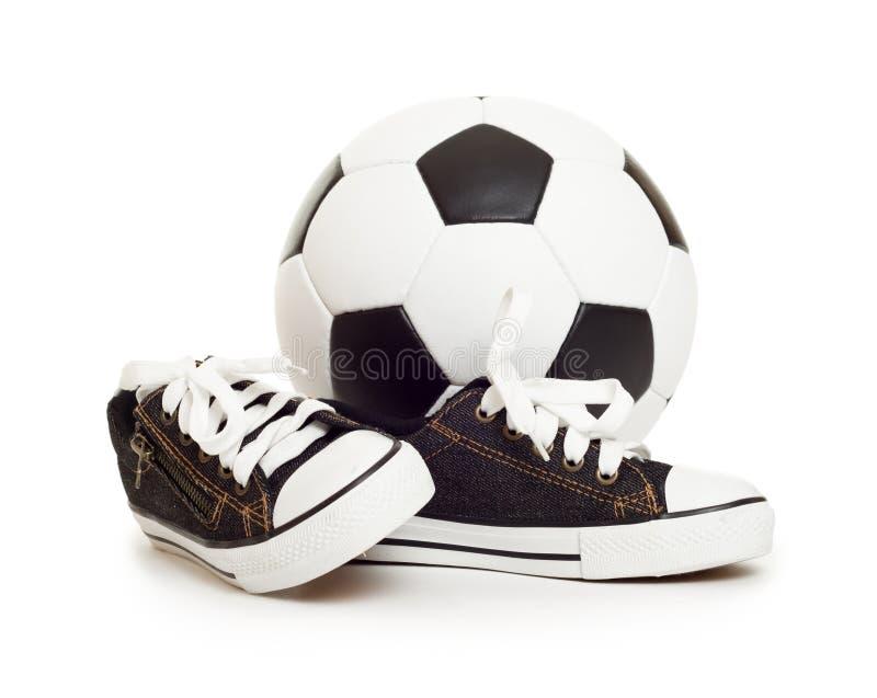 Zapatos de la bola y del deporte de fútbol en blanco imágenes de archivo libres de regalías