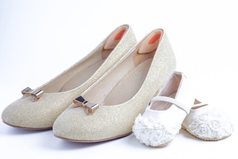 Zapatos de la mujer y de bebé en el fondo blanco fotografía de archivo