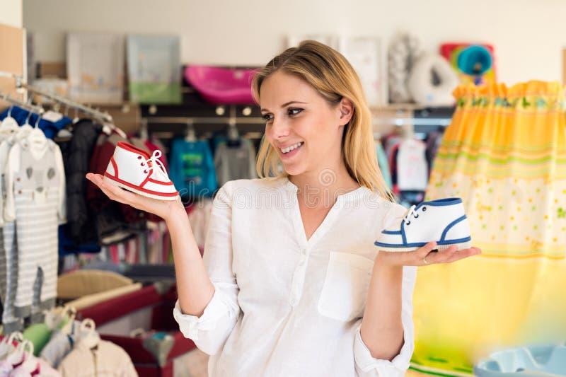 Zapatos de las compras de la mujer embarazada para su bebé foto de archivo libre de regalías