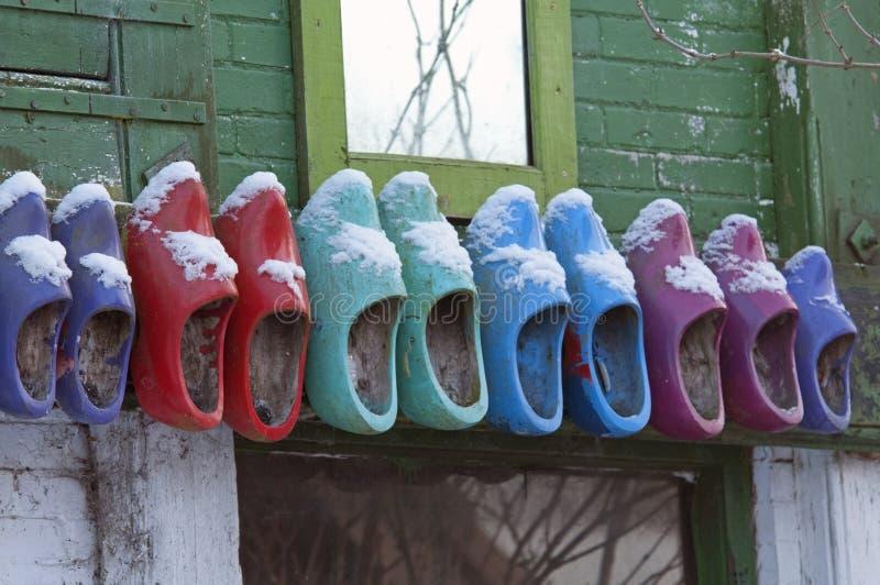 Zapatos de madera coloreados en la pared fotos de archivo libres de regalías