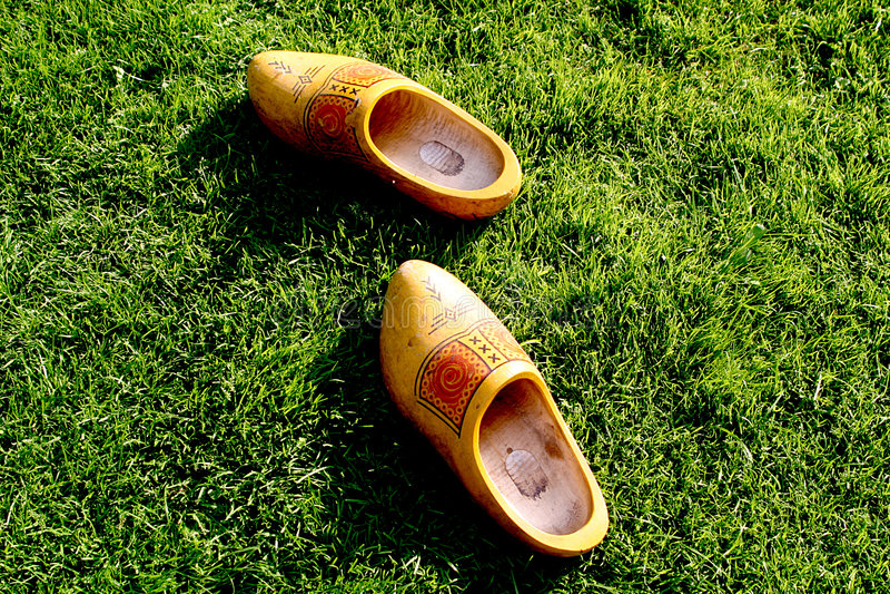 Zapatos de madera en la hierba foto de archivo
