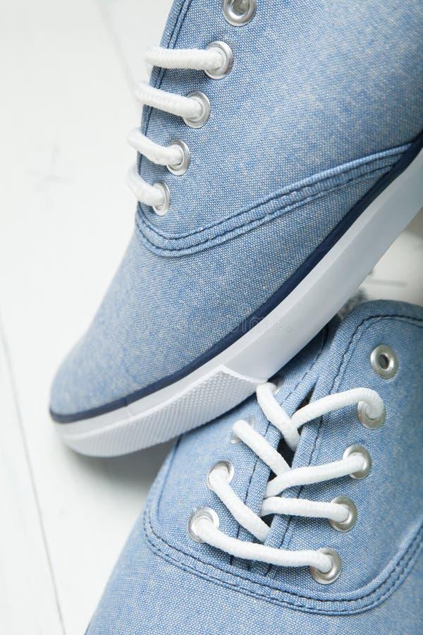 Zapatos de moda en un fondo de madera ligero, primer blanco de los cordones foto de archivo