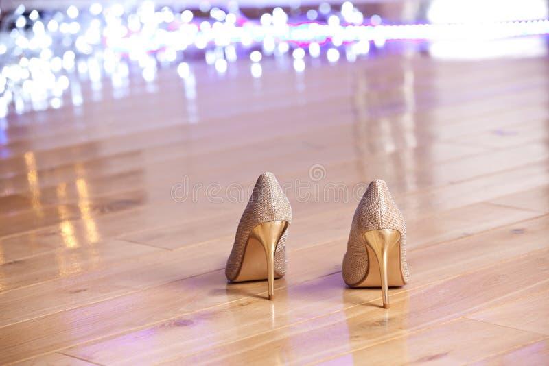Zapatos de tacón alto de las mujeres elegantes del oro fotos de archivo libres de regalías