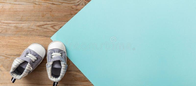 Zapatos del bebé en el fondo azul y de madera en colores pastel, bandera imagenes de archivo