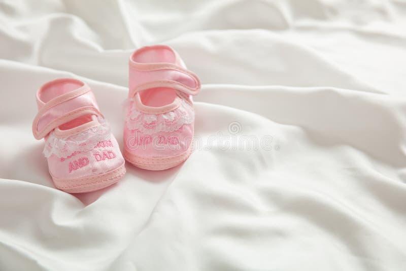 Zapatos del bebé en el satén blanco, espacio de la copia foto de archivo libre de regalías