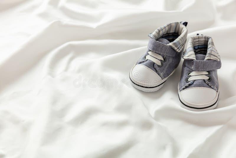 Zapatos del bebé en el satén blanco, espacio de la copia imagen de archivo libre de regalías