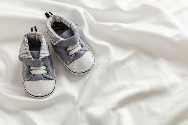 Zapatos del bebé en el satén blanco, espacio de la copia imagenes de archivo
