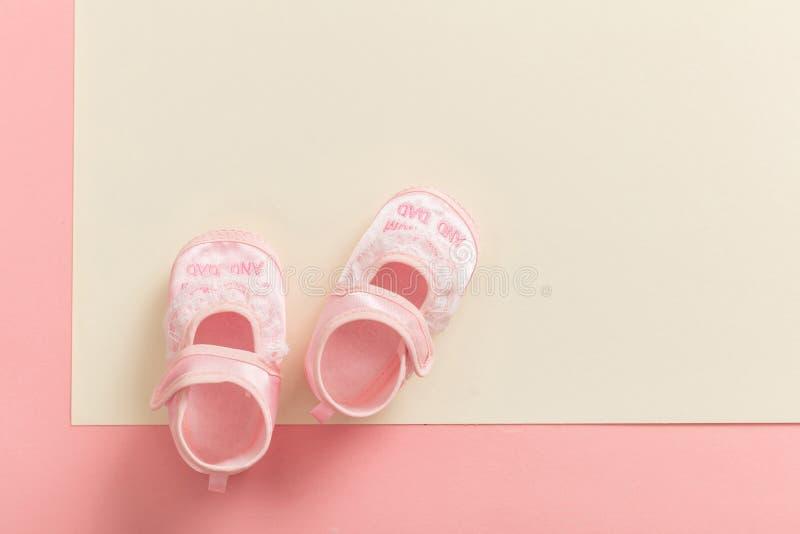 Zapatos del bebé en fondo de los colores en colores pastel imagenes de archivo