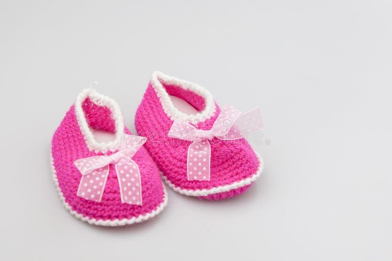 Zapatos del beb? en el fondo blanco, bandera, espacio de la copia Botines hechos punto del beb? imagen de archivo