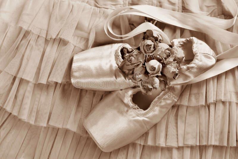 Zapatos del pointe del ballet que mienten en el vestido de Tulle en sepia fotografía de archivo