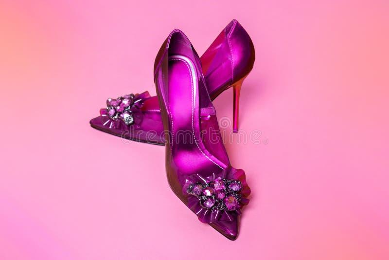 Zapatos del ` s de las mujeres elegantes con las decoraciones del tacón alto y del encanto en un fondo amarillo fotos de archivo