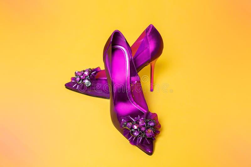 Zapatos del ` s de las mujeres elegantes con las decoraciones del tacón alto y del encanto en un fondo amarillo imagen de archivo libre de regalías