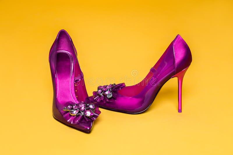 Zapatos del ` s de las mujeres elegantes con las decoraciones del tacón alto y del encanto en un fondo amarillo foto de archivo libre de regalías