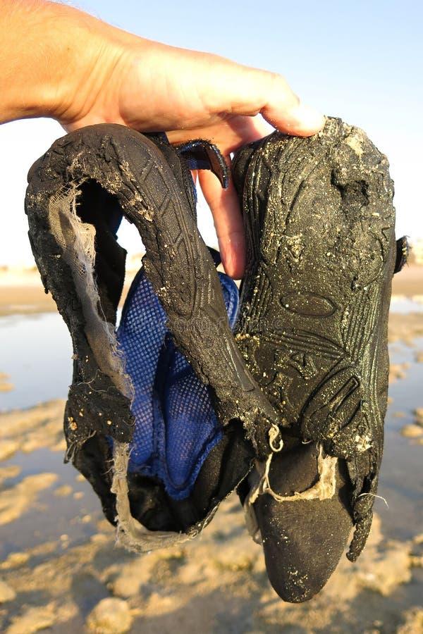 Zapatos en el agua que no resistió el caminar en el acantilado del mar fotografía de archivo