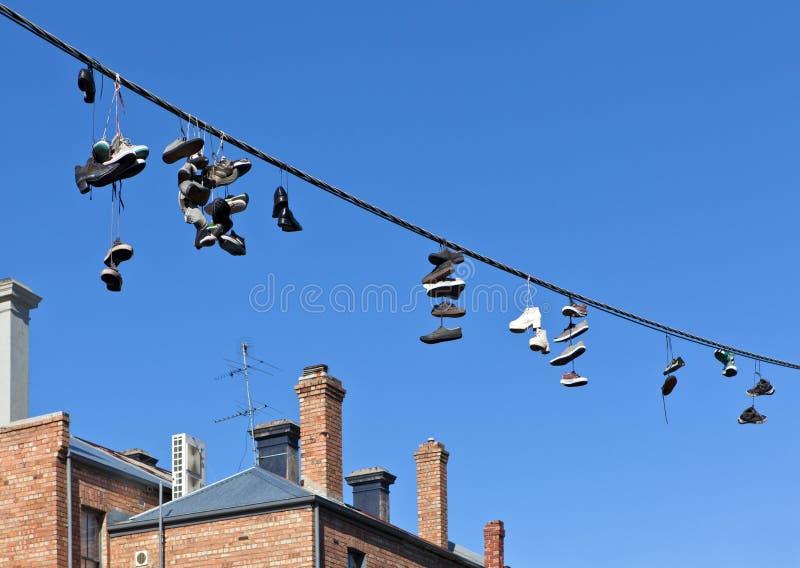 Zapatos en el alambre de teléfono fotografía de archivo