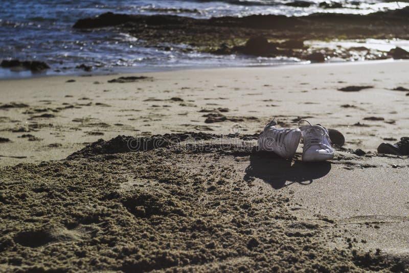 Zapatos en la playa con el sitio para el texto fotografía de archivo
