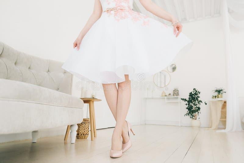 Zapatos en las piernas de una muchacha en un vestido blanco fotos de archivo