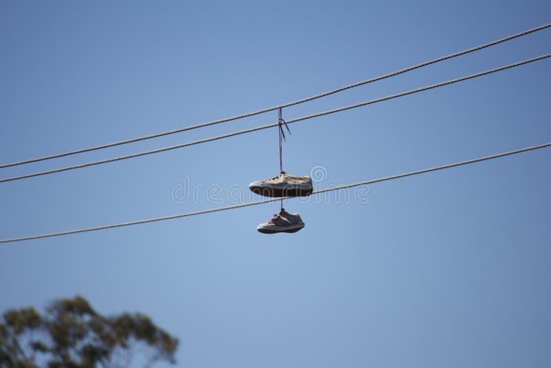 Zapatos en un alambre de teléfono foto de archivo libre de regalías