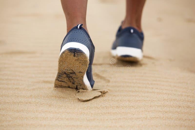 Zapatos femeninos del ángulo bajo que caminan en arena fotos de archivo libres de regalías