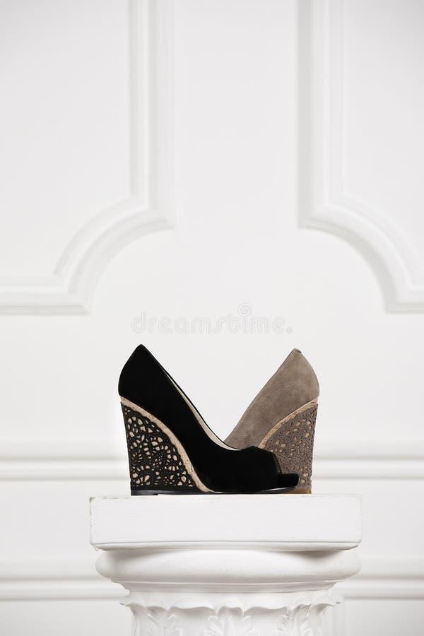 Zapatos femeninos hermosos en una columna blanca de la antigüedad del soporte. imagenes de archivo