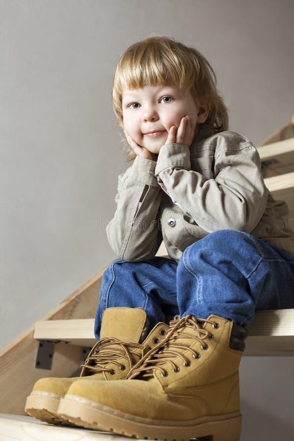 Zapatos grandes para llenar los pies del niño en zapato grande fotografía de archivo