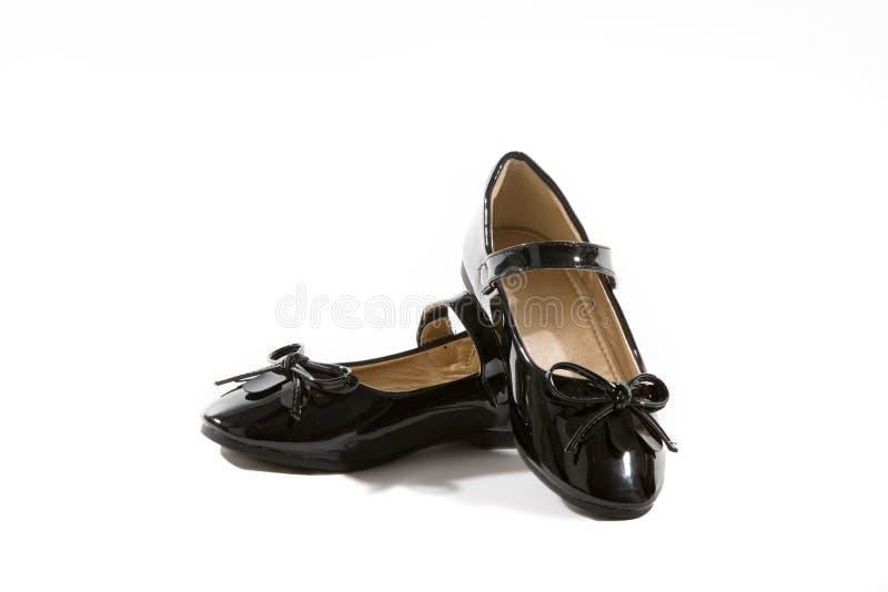 Zapatos negros de los planos de las muchachas del charol con los arcos imagen de archivo libre de regalías