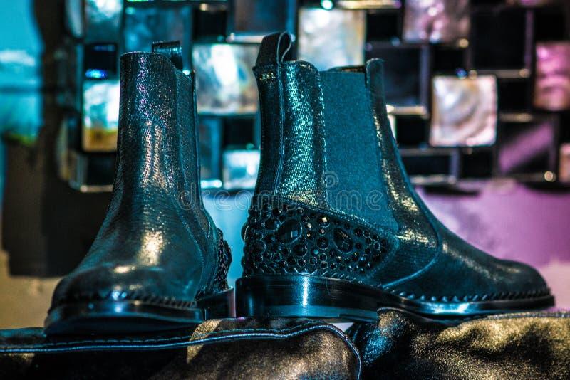 Zapatos negros en un sofá púrpura imagenes de archivo