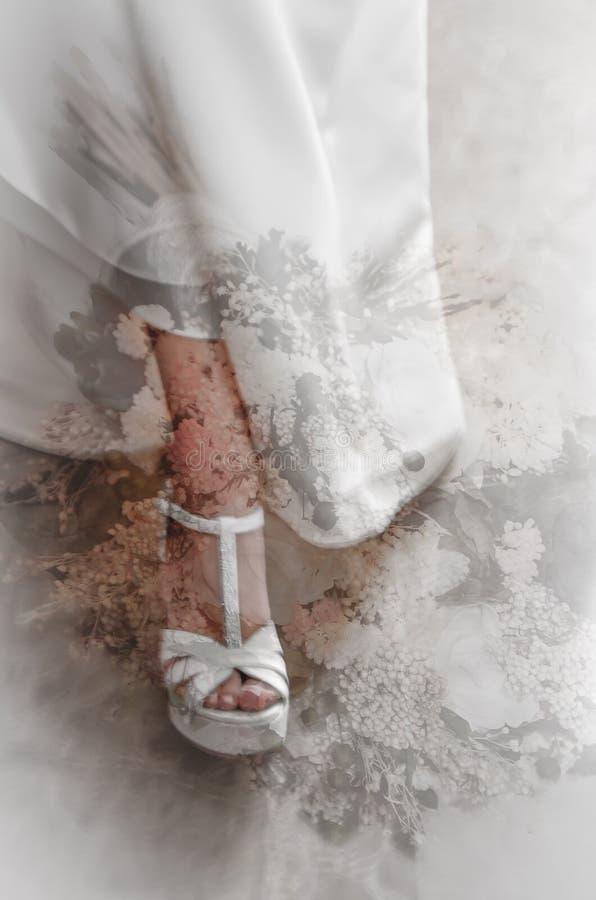 Zapatos nupciales entre la niebla de las flores imagen de archivo libre de regalías