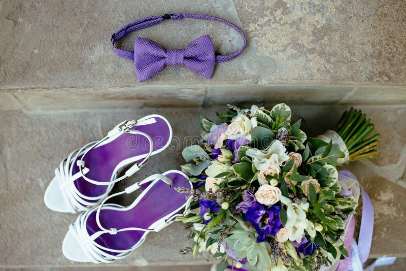 Zapatos p?rpuras de la corbata de lazo del ramo de los accesorios que se casan fotos de archivo