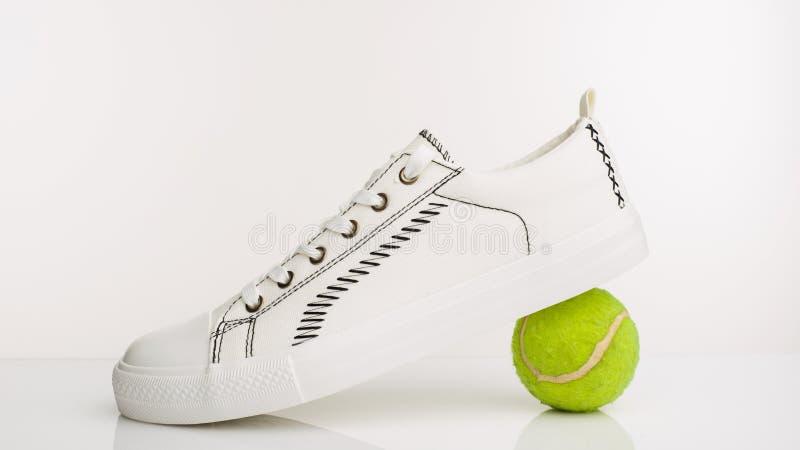Zapatos para andar blancos de moda con la pelota de tenis en un fondo blanco imagenes de archivo