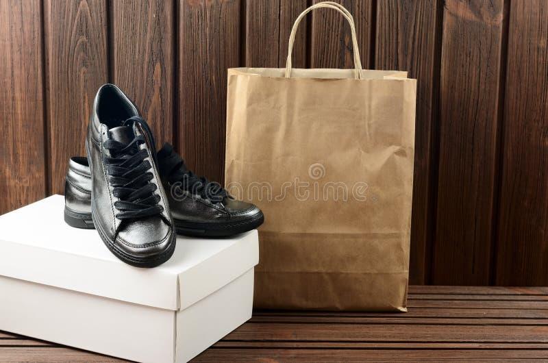 Zapatos para mujer trandy metálicos del cuero superior en backg de madera marrón fotografía de archivo