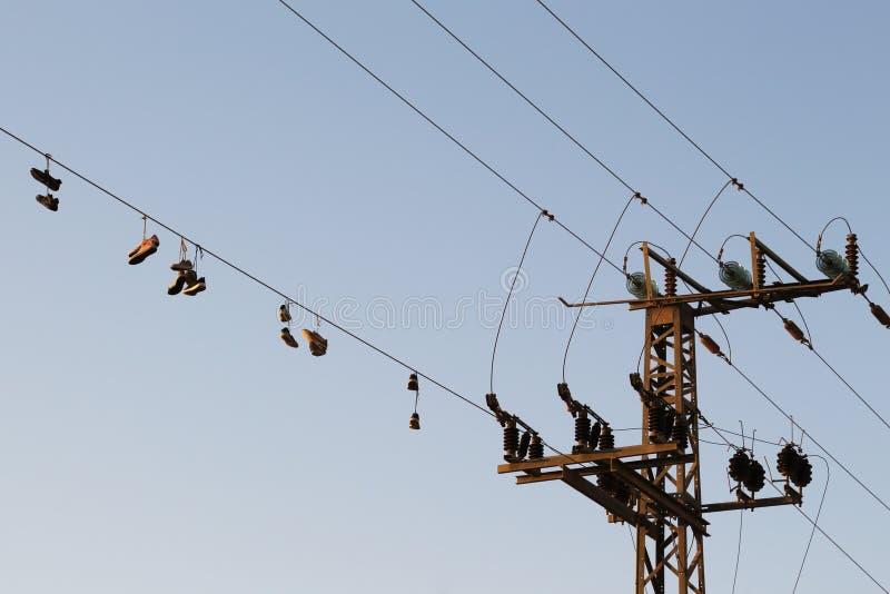 Zapatos que cuelgan en un cable eléctrico sobre la calle imagen de archivo libre de regalías