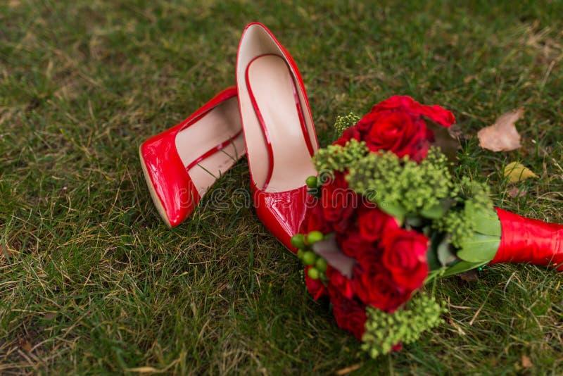 Zapatos rojos de la boda de la moda femenina con el ramo del ` s de la novia de rosas rojas y de bayas verdes en fondo de la hier fotos de archivo
