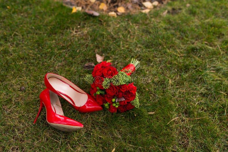 Zapatos rojos de la boda de la moda femenina con el ramo del ` s de la novia de rosas rojas y de bayas verdes en fondo de la hier foto de archivo libre de regalías