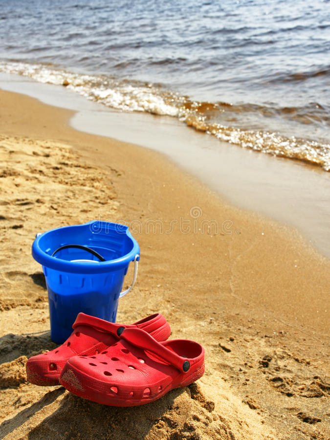 Zapatos rojos verticales en la playa fotografía de archivo