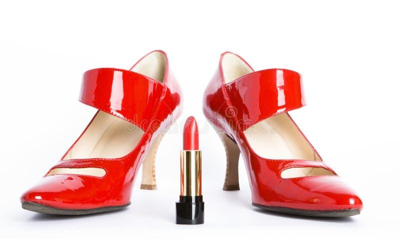Zapatos rojos y lápiz labial rojo imágenes de archivo libres de regalías
