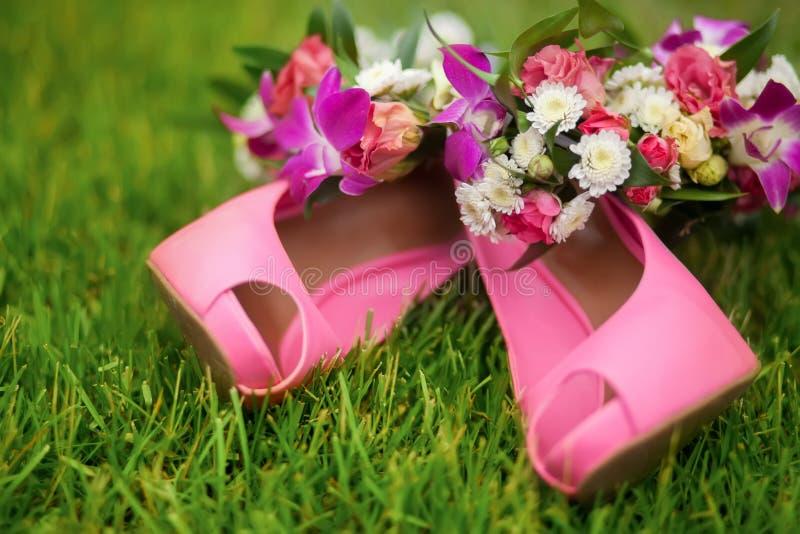 Zapatos rosados con el ramo rosado en la hierba, día de boda imagenes de archivo
