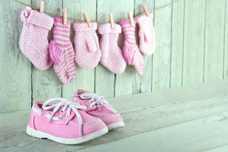 Zapatos rosados del niño en fondo verde claro de madera fotografía de archivo