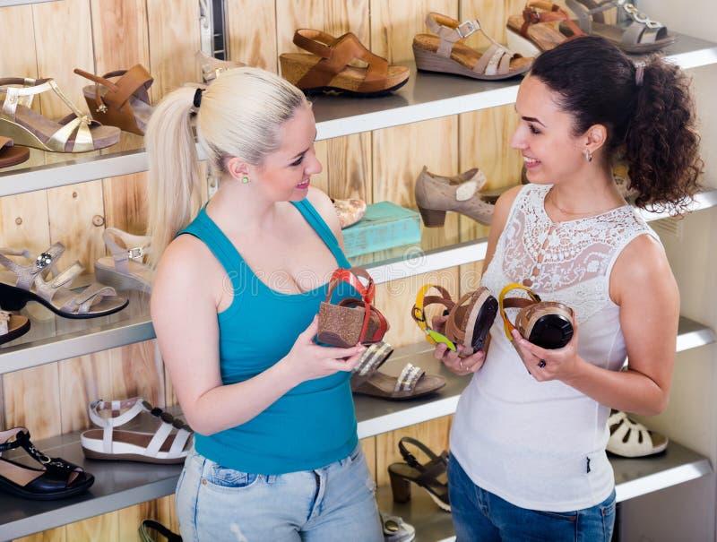 Zapatos rubios y morenos del verano de la compra en la tienda moderna imagenes de archivo