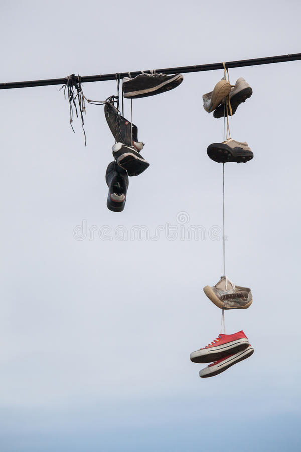 Zapatos viejos que cuelgan en el alambre - cambio de la vida fotografía de archivo