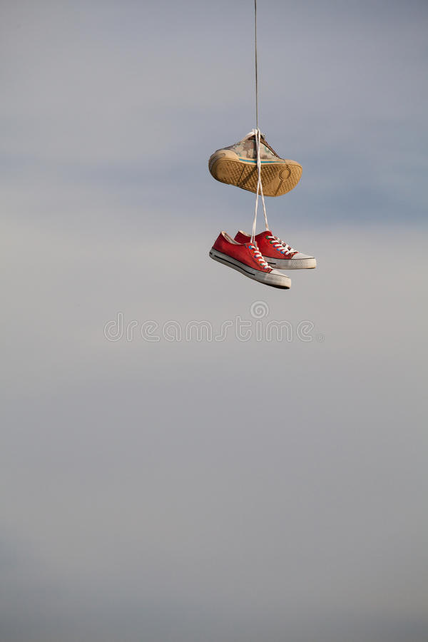 Zapatos viejos que cuelgan en el alambre - cambio de la vida imagen de archivo libre de regalías