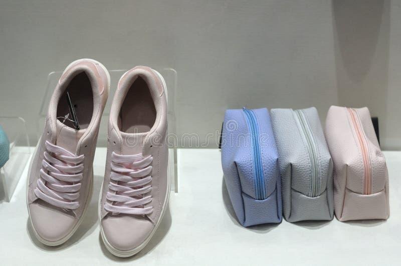 Zapatos y bolsos de la zapatilla de deporte en la exhibición foto de archivo