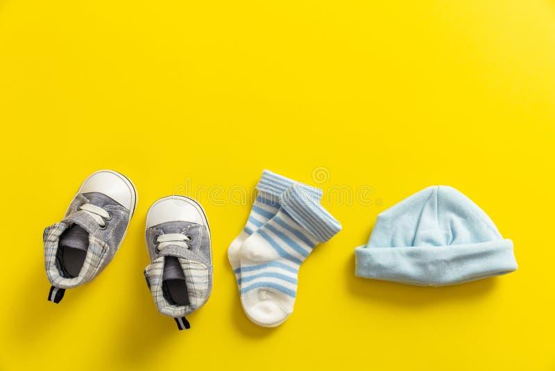 Zapatos y calcetines del bebé en fondo amarillo brillante imagen de archivo
