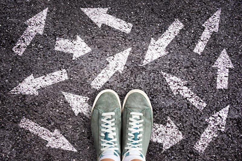 Zapatos y flechas de la zapatilla de deporte que señalan en diversas direcciones en el asfalto, concepto bien escogido foto de archivo libre de regalías